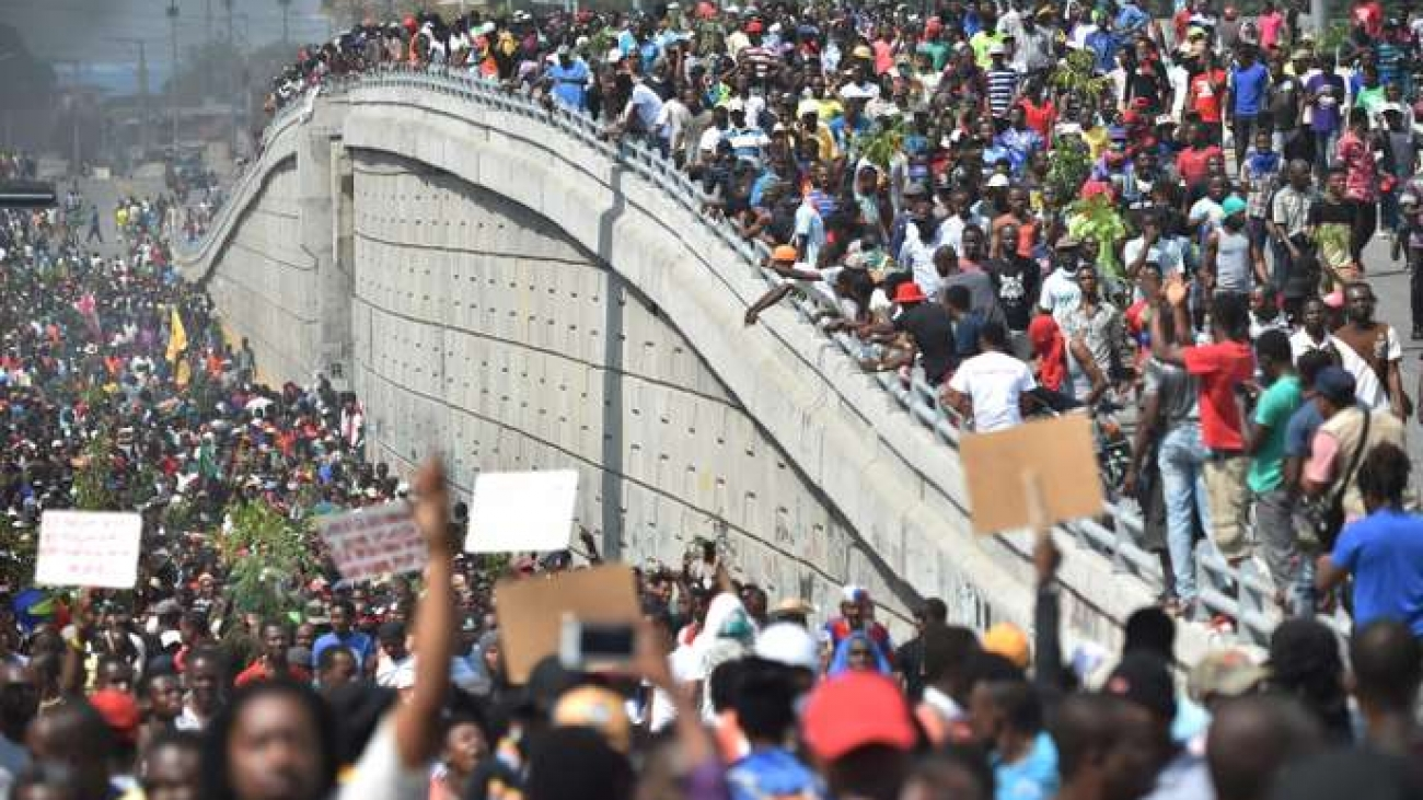Demonstrators march through the streets of Port-au-Prince, on February 7, 2019. Demonstrators demanded the resignation of Haitian President Jovenel Moise, as protesters blocked streets and lit tires during their march in the Haitian capital. The protesters also demonstrated against the Petrocaribe fund, as last week a new report on the spending of money from the Petrocaribe fund was presented. / AFP / HECTOR RETAMAL